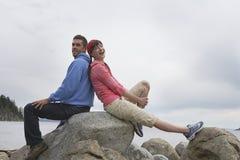 Couples se reposant de nouveau au dos sur des roches contre l'océan Images stock