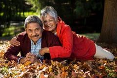 Couples se reposant dessus au parc pendant l'automne Images stock