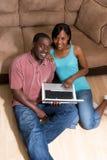 Couples se reposant devant le divan avec COM d'ordinateur portatif photos stock