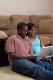 Couples se reposant devant le divan avec COM d'ordinateur portatif photo stock
