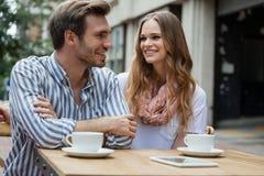 Couples se reposant par la table au café de trottoir Image libre de droits