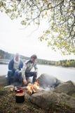 Couples se reposant près du feu sur au bord du lac Image stock