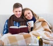 Couples se reposant sous la couverture avec le livre Photos libres de droits