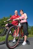 Couples se reposant sur des vélos - verticale Image libre de droits