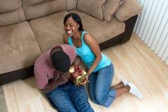 Couples se reposant sur l'étage riant retenant un cadeau photos stock