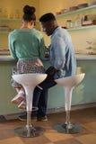 Couples se reposant sur la chaise près du compteur Images libres de droits
