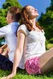 Couples se reposant sur la pelouse de parc appréciant le soleil Photos libres de droits