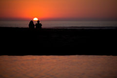 Couples se reposant sur la plage pendant le coucher du soleil Photo stock