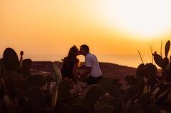 Couples se reposant sur la roche le soir Image libre de droits