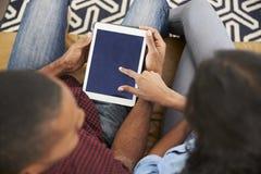 Couples se reposant sur la Tablette de Sofa At Home Looking At Digital Images libres de droits