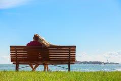 Couples se reposant sur le banc de stationnement Images stock