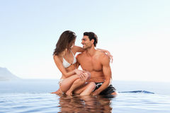 Couples se reposant sur le bord de piscine ensemble Photo libre de droits