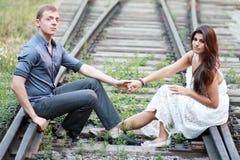 Couples se reposant sur le chemin de fer Images stock