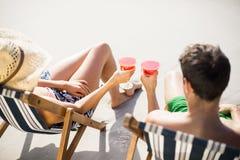 Couples se reposant sur le fauteuil avec la boisson de cocktail Photo stock