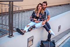 Couples se reposant sur le mur et étreindre Photo stock