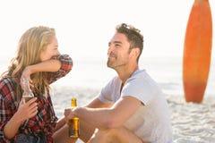 Couples se reposant sur le sable à la plage Photographie stock libre de droits