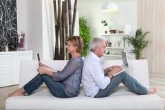 Couples se reposant sur le sofa Photos libres de droits