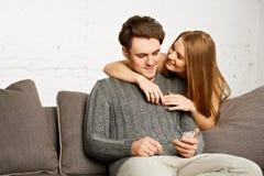 Couples se reposant sur le sofa, observant quelque chose au téléphone portable Photographie stock