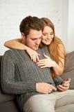 Couples se reposant sur le sofa, observant quelque chose au téléphone portable Image stock