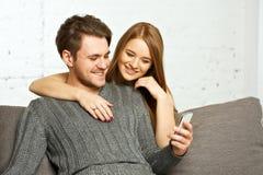 Couples se reposant sur le sofa, observant quelque chose au téléphone portable Photos stock