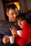 Couples se reposant sur le sofa par le feu de bois confortable Photo stock