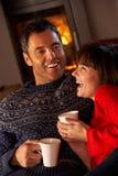 Couples se reposant sur le sofa par le feu de bois confortable Images libres de droits