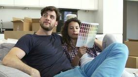 Couples se reposant sur Sofa Looking At Paint Charts banque de vidéos