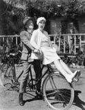 Couples se reposant sur une bicyclette de tandem (toutes les personnes représentées ne sont pas plus long vivantes et aucun domai Photo stock
