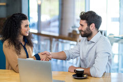 Couples se serrant la main dans le café Image stock