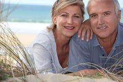 Couples se situant dans les dunes de sable Photographie stock