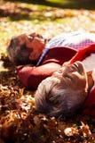 Couples se situant en parc pendant l'automne Photo libre de droits