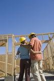 Couples se tenant à une construction de logement non finie Image stock