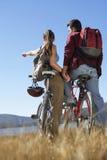 Couples se tenant ainsi que des bicyclettes À CÔTÉ du lac Image stock