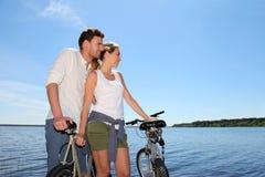Couples se tenant prêt le lac avec des vélos Images libres de droits