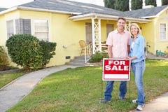 Couples se tenant prêt pour le signe de vente en dehors de la maison Photo stock