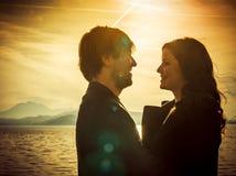 Couples se tenant prêt le lac à la lumière du soleil Photos stock