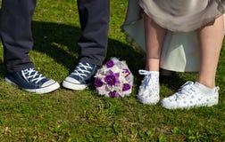 Couples se tenant sur l'herbe Jeunes mariés dans des espadrilles Photos libres de droits
