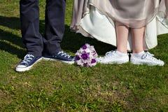 Couples se tenant sur l'herbe Jeunes mariés dans des espadrilles Image libre de droits