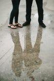Couples se tenant sur la réflexion de rue dans l'eau. Image libre de droits
