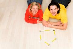 Couples se trouvant sur l'étage dans la maison neuve Photographie stock libre de droits