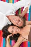 Couples se trouvant sur l'essuie-main de plage Images libres de droits
