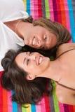 Couples se trouvant sur l'essuie-main de plage Photographie stock libre de droits