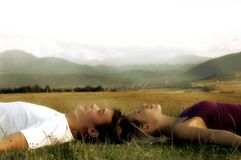 Couples se trouvant sur l'herbe Photos libres de droits