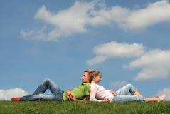 Couples se trouvant sur l'herbe Images libres de droits