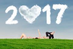 Couples se trouvant sur l'herbe avec le nuage 2017 Photo stock