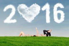 Couples se trouvant sur l'herbe sous les numéros 2016 Photo stock