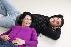 Couples se trouvant sur l'étage en bois Photographie stock libre de droits