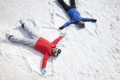 Couples se trouvant sur la neige faisant l'ange de neige Photos stock