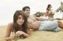 Couples se trouvant sur la plage Image stock