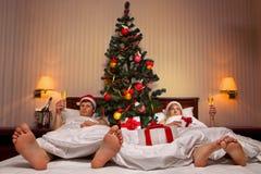 Couples se trouvant sur le bâti avec l'arbre de Noël Photos stock